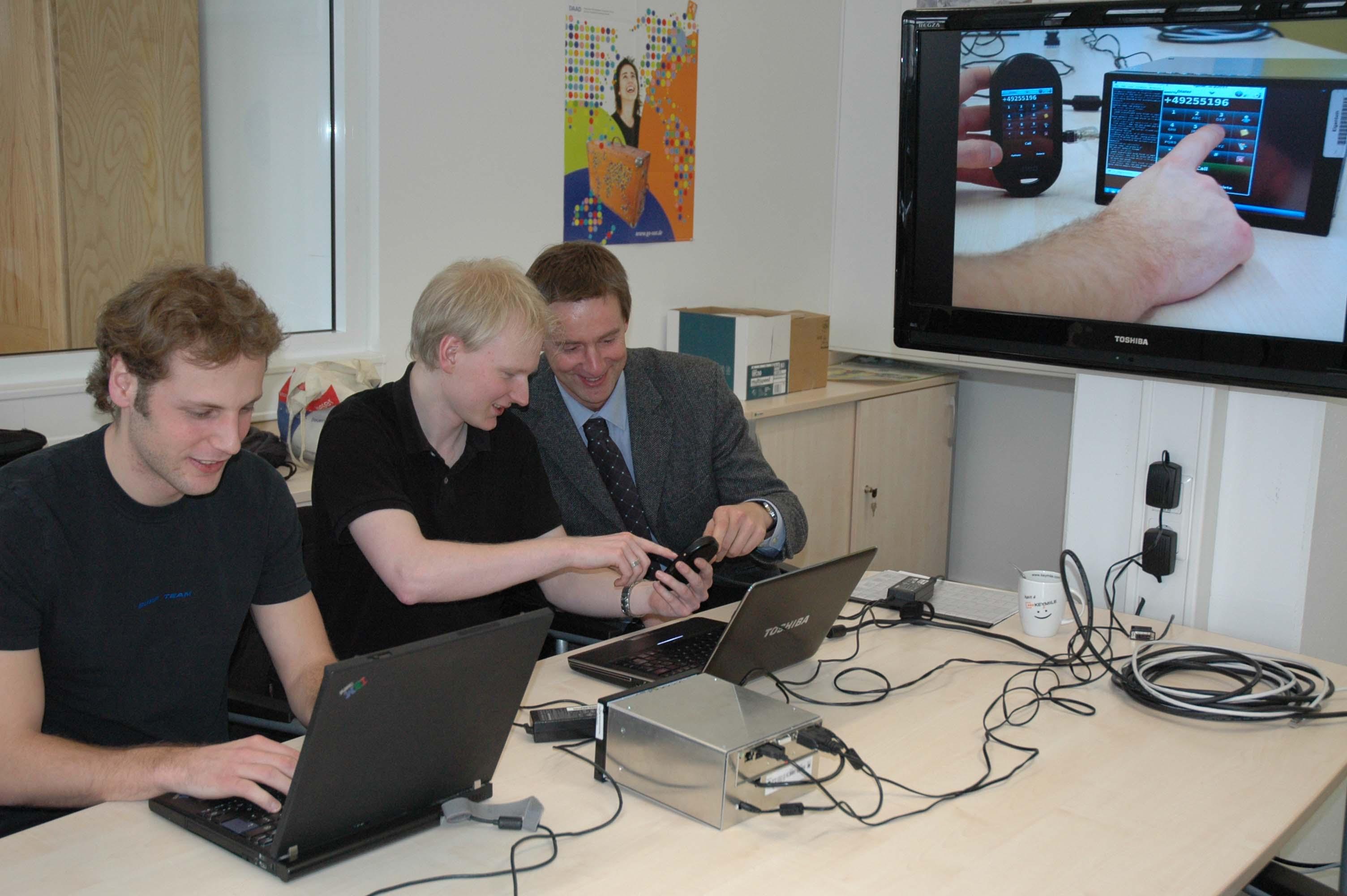 Drei Personen vor Computern im Labor