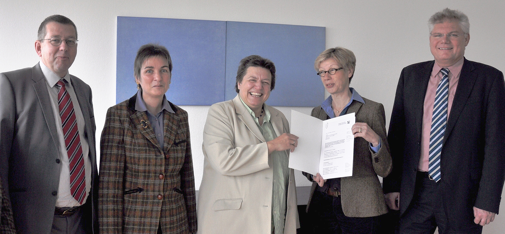 Gruppenbild mit fünf Personen nach Überreichung einer Urkunde.