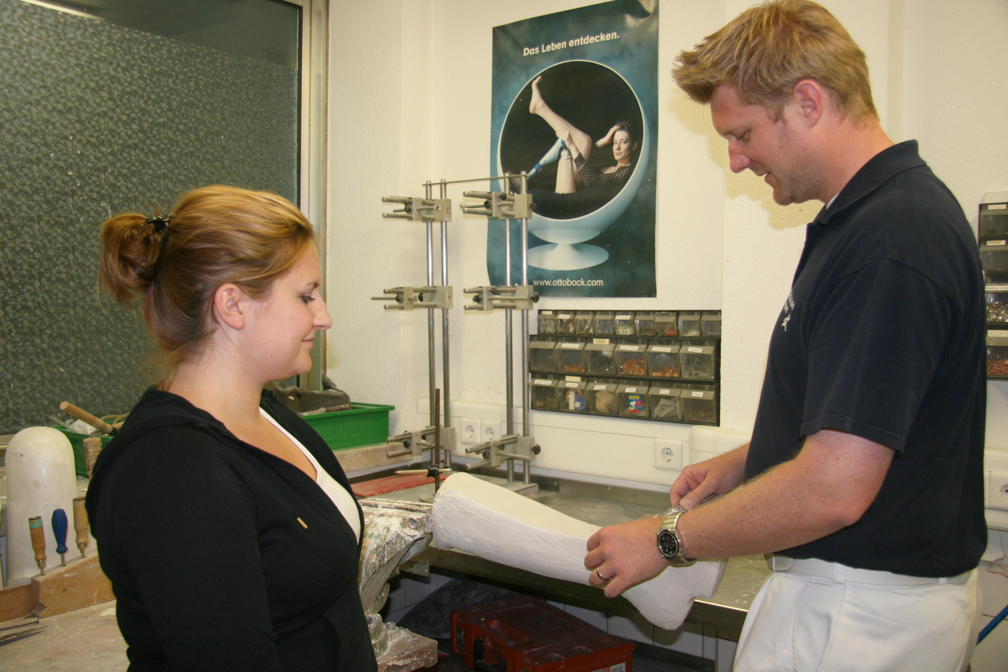 Orthopädietechnik-Meister Tobias Quarg zeigt der Auszubildenden, wie ein Gipsmodell in Form geraspelt wird.