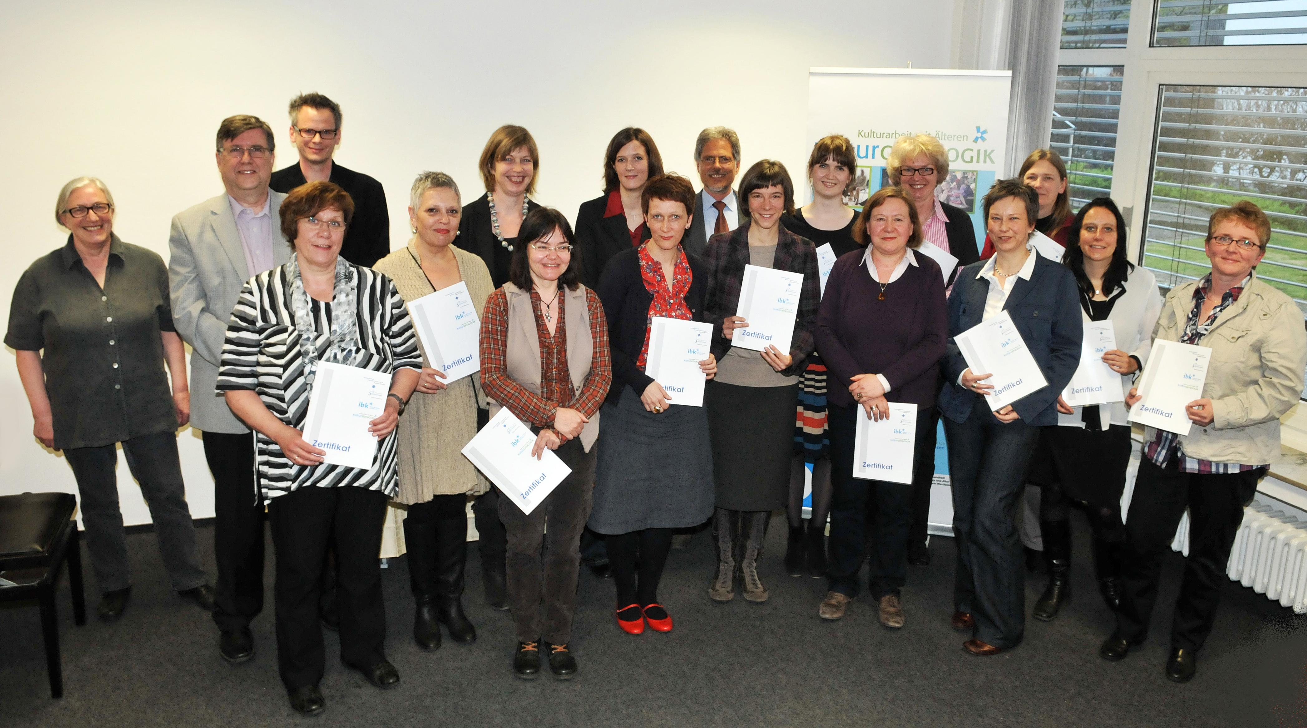 Gruppenfoto der 14 Teilnehmerinnen des Zertifikatskurs Kulturgeragogik mit Gratulanten Dr. Claus Eppe, Magdalena Megler, Stefan Gesmann und Prof. Dr. Hans-Hermann Wickel.