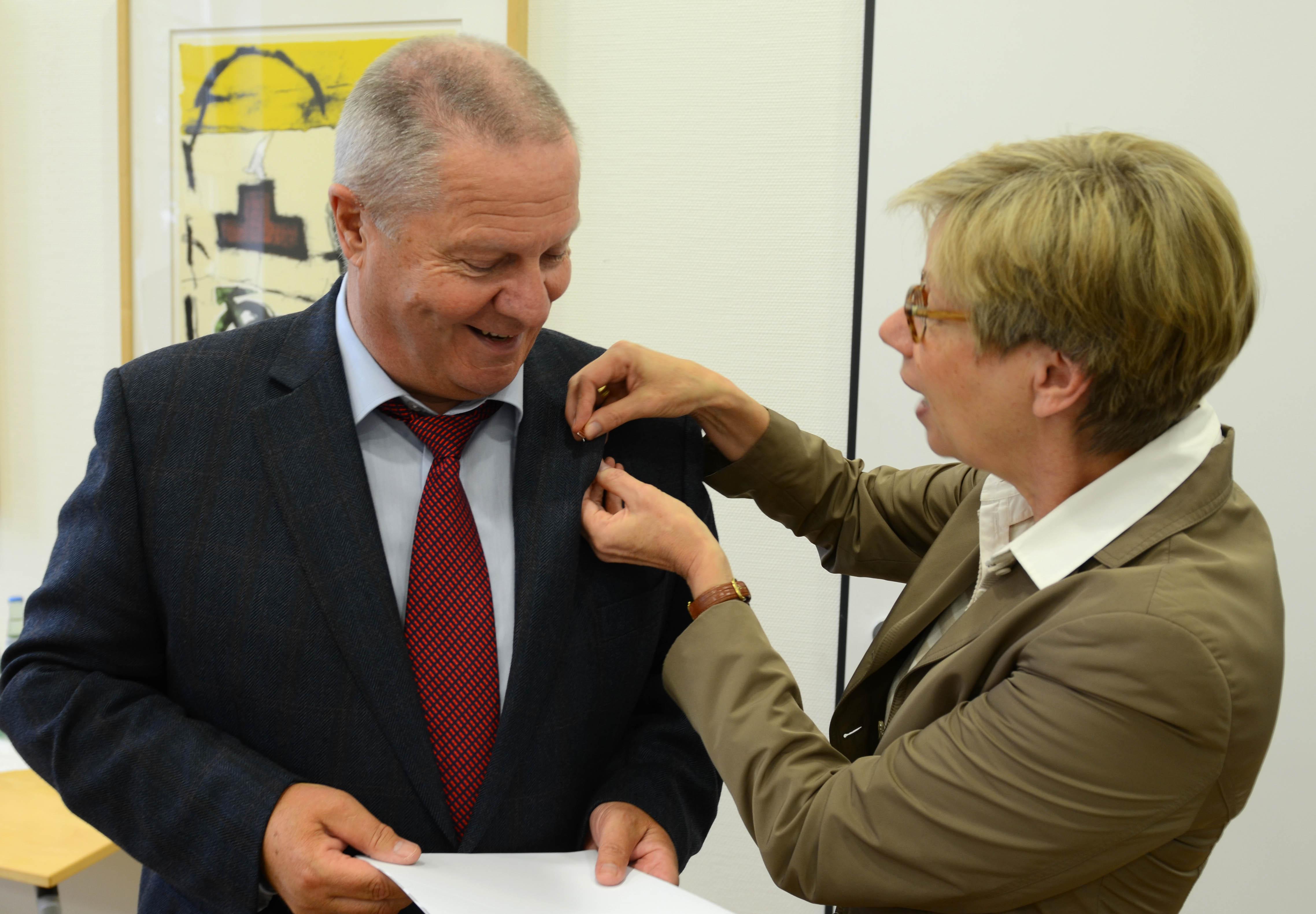 Präsidentin steckt Mann eine Nadel ans Revers.