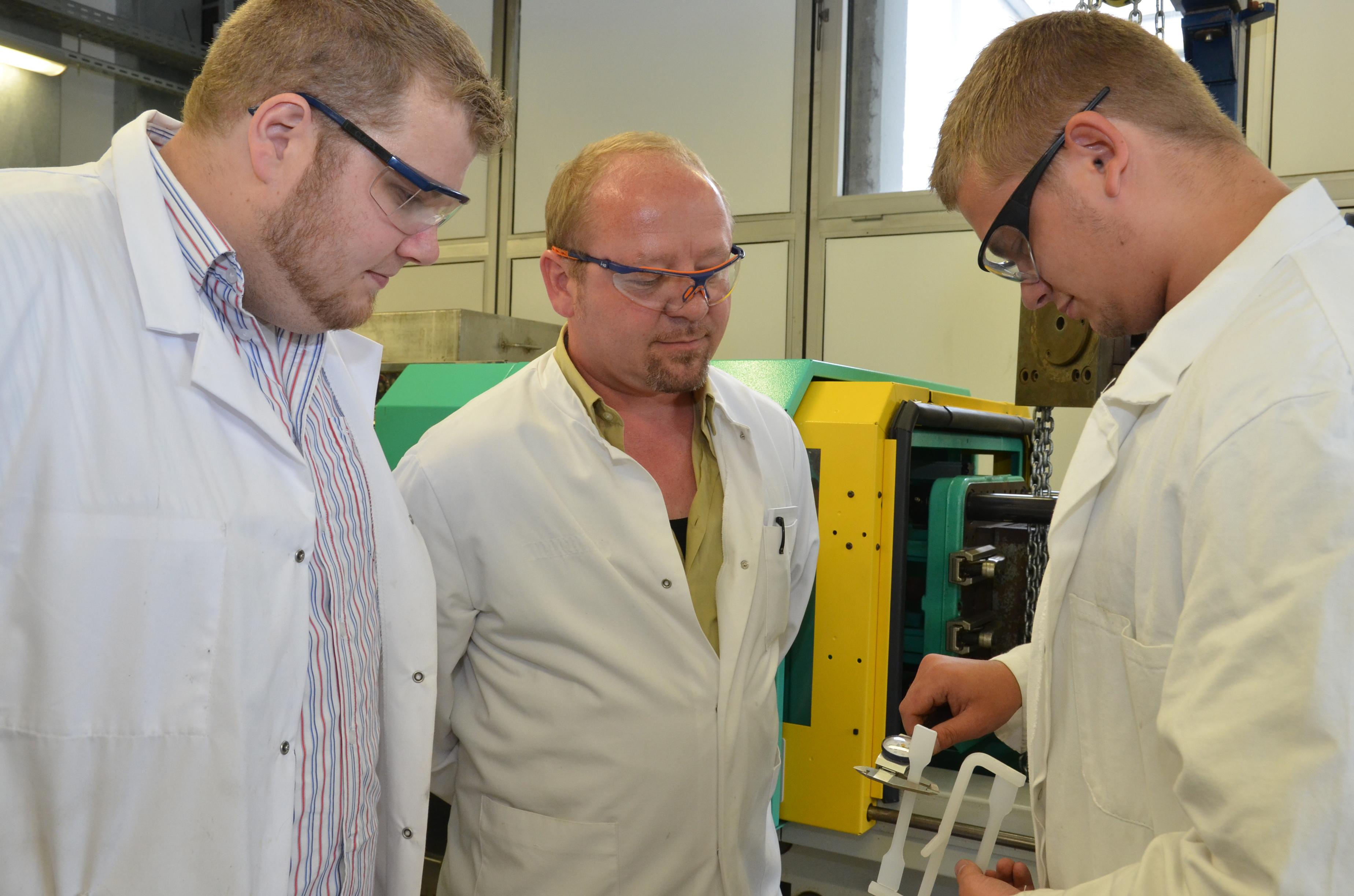 Zwei Auszubildende mit Ausbildungsleiter im Kunststofflabor
