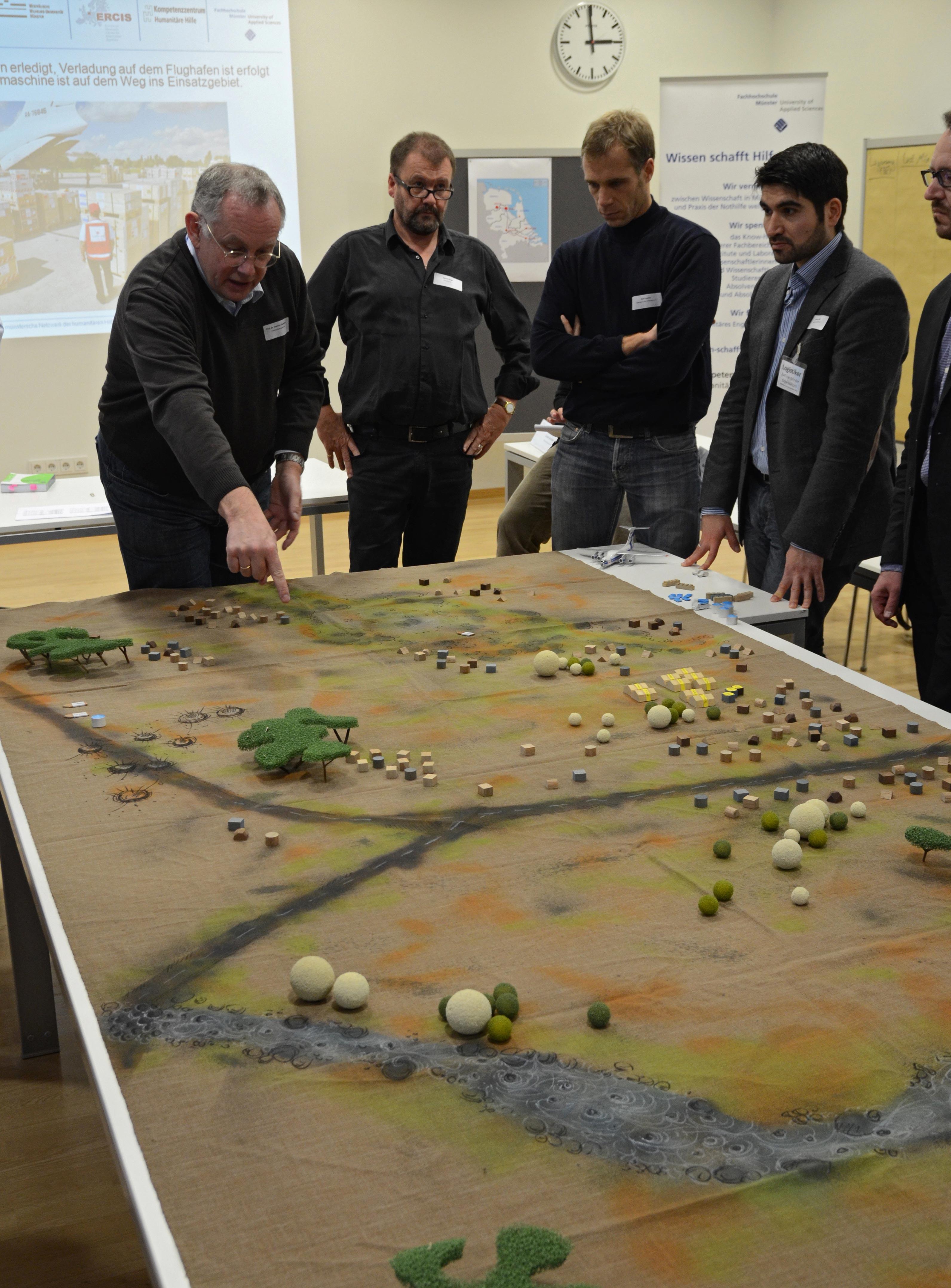 """Prof. Dr. Joachim Gardemann mit Workshop-Teilnehmern vor dem Planspiel """"Disaster Response Model""""."""