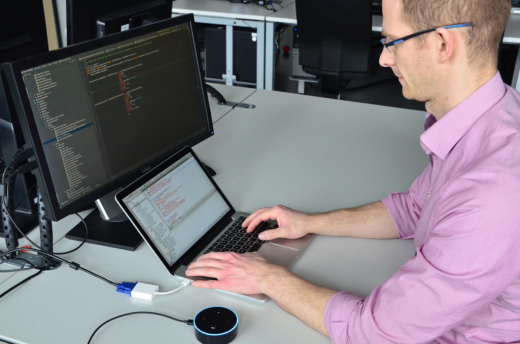 Markus Boese vor seinem Laptop mit dem kleinen runden Gerät Echo Dot.
