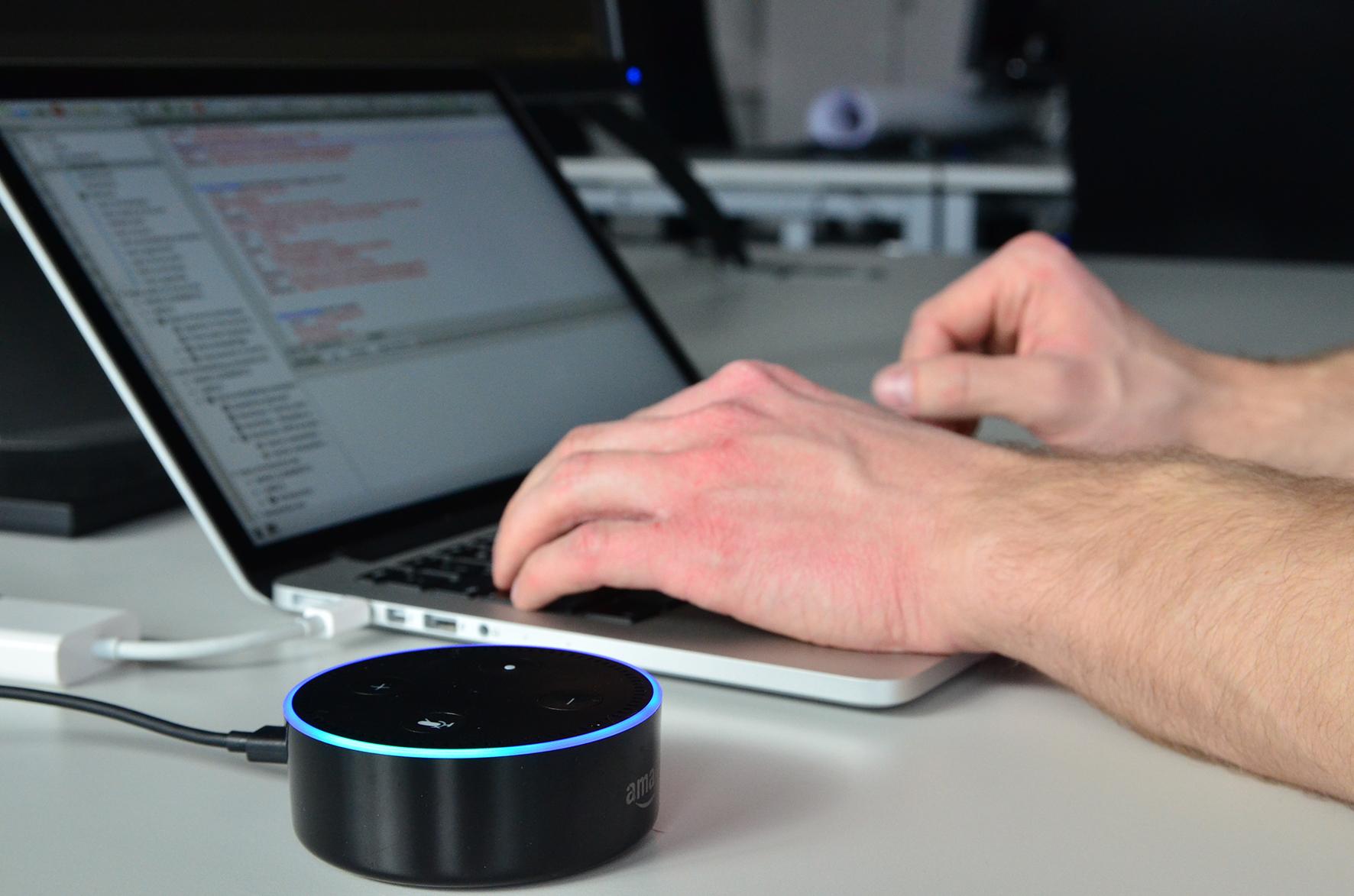 Der äußere Ring des Geräts leuchtet türkis-blau, im Hintergrund Hände tippend auf einer Laptoptastatur.