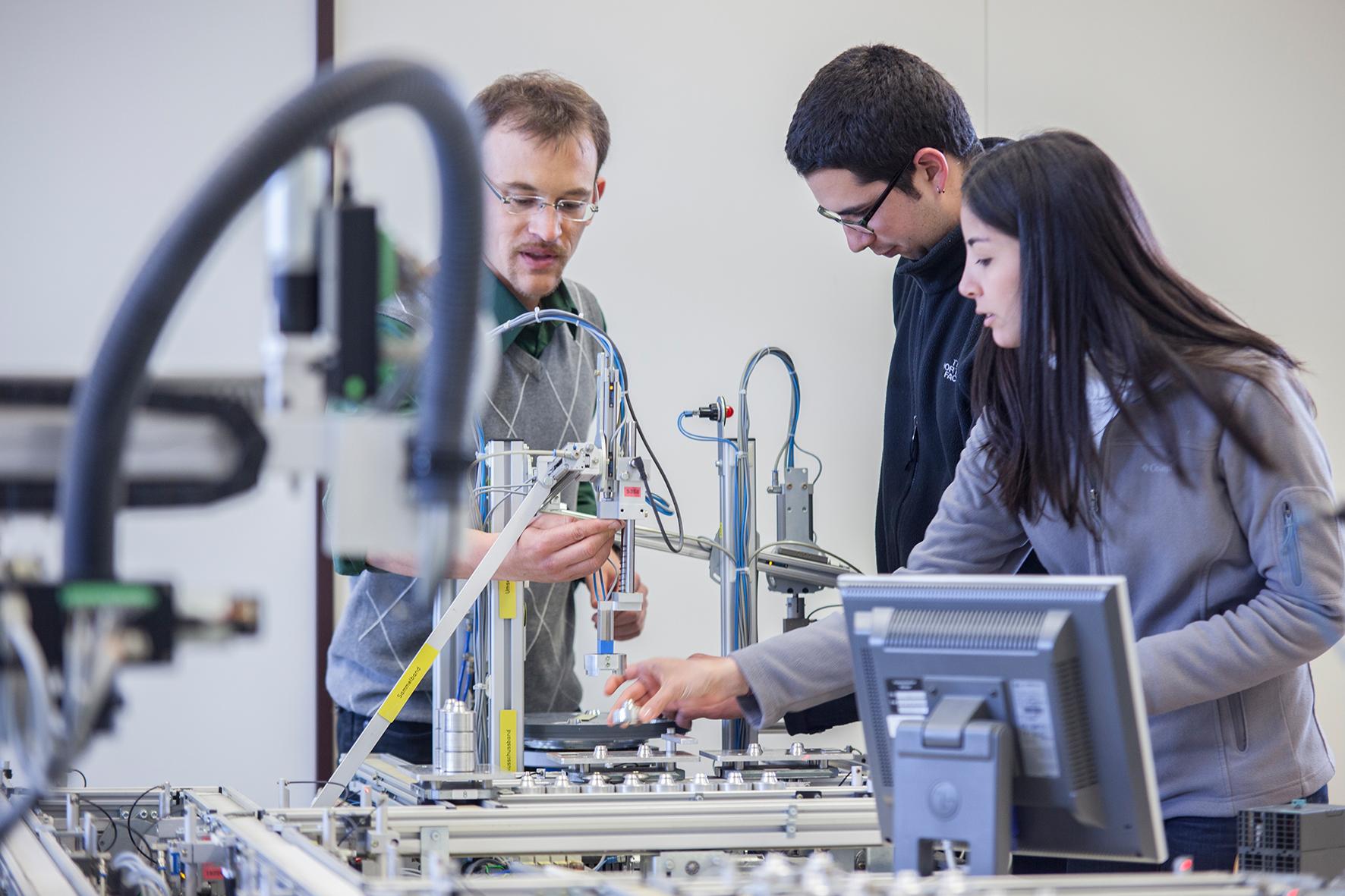 Professor, ein Student und eine Studentin in der Modellfabrik