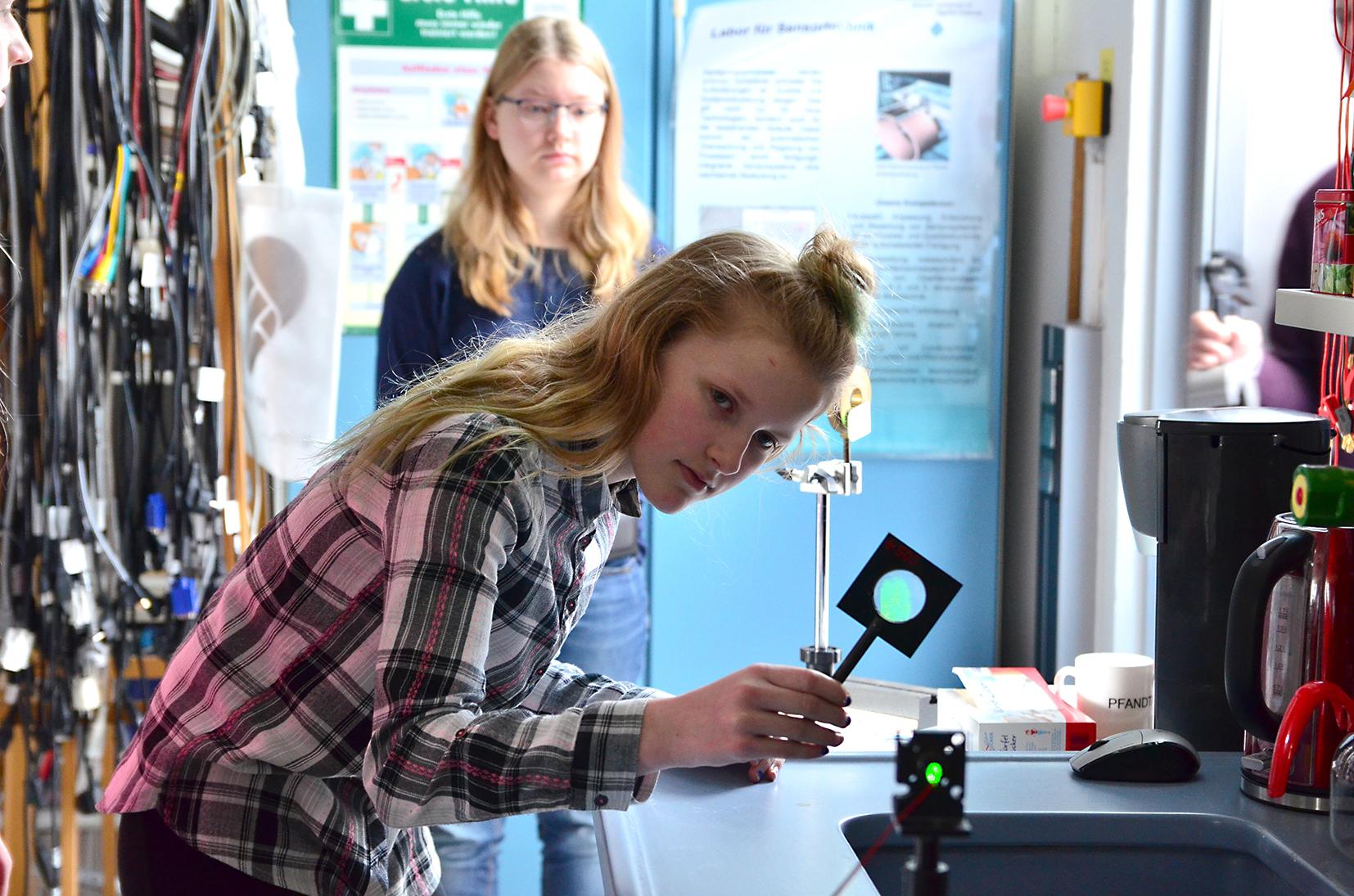 Schülerin experimentiert mit einem Laserstrahl.