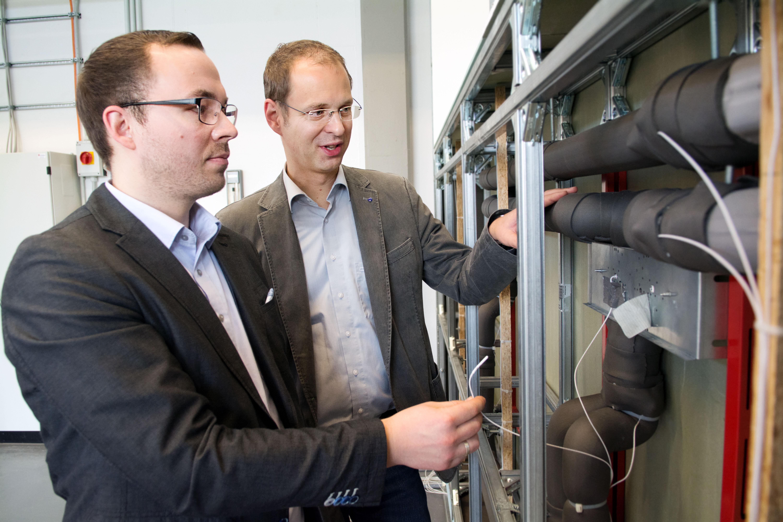 Stefan Brodale hält einen Temperaturfühler, Prof. Dr. Carsten Bäcker tastet über die Warmwasserleitung