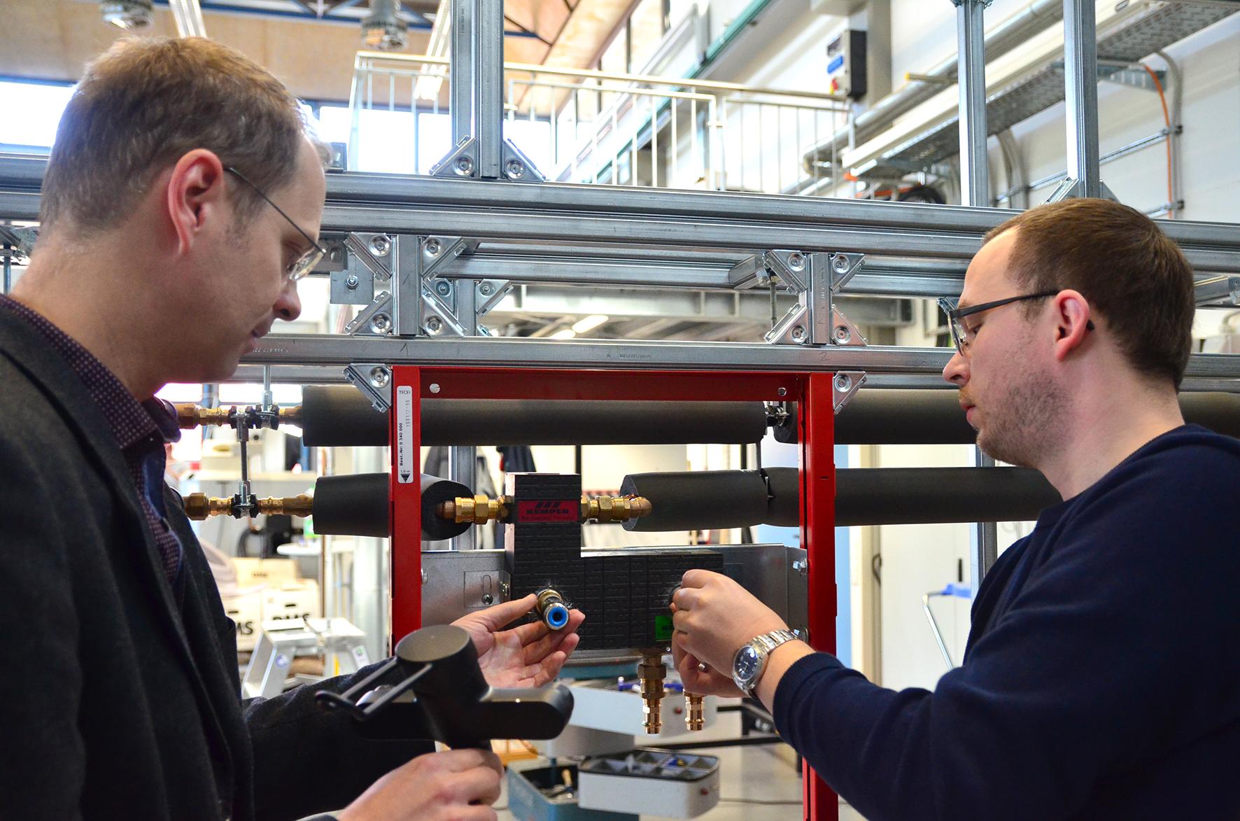 Prof. Dr. Carsten Bäcker und Stefan Brodale schrauben eine Waschbeckenarmatur an ihre selbst gebaute Vorwand inklusive Hohlraum.
