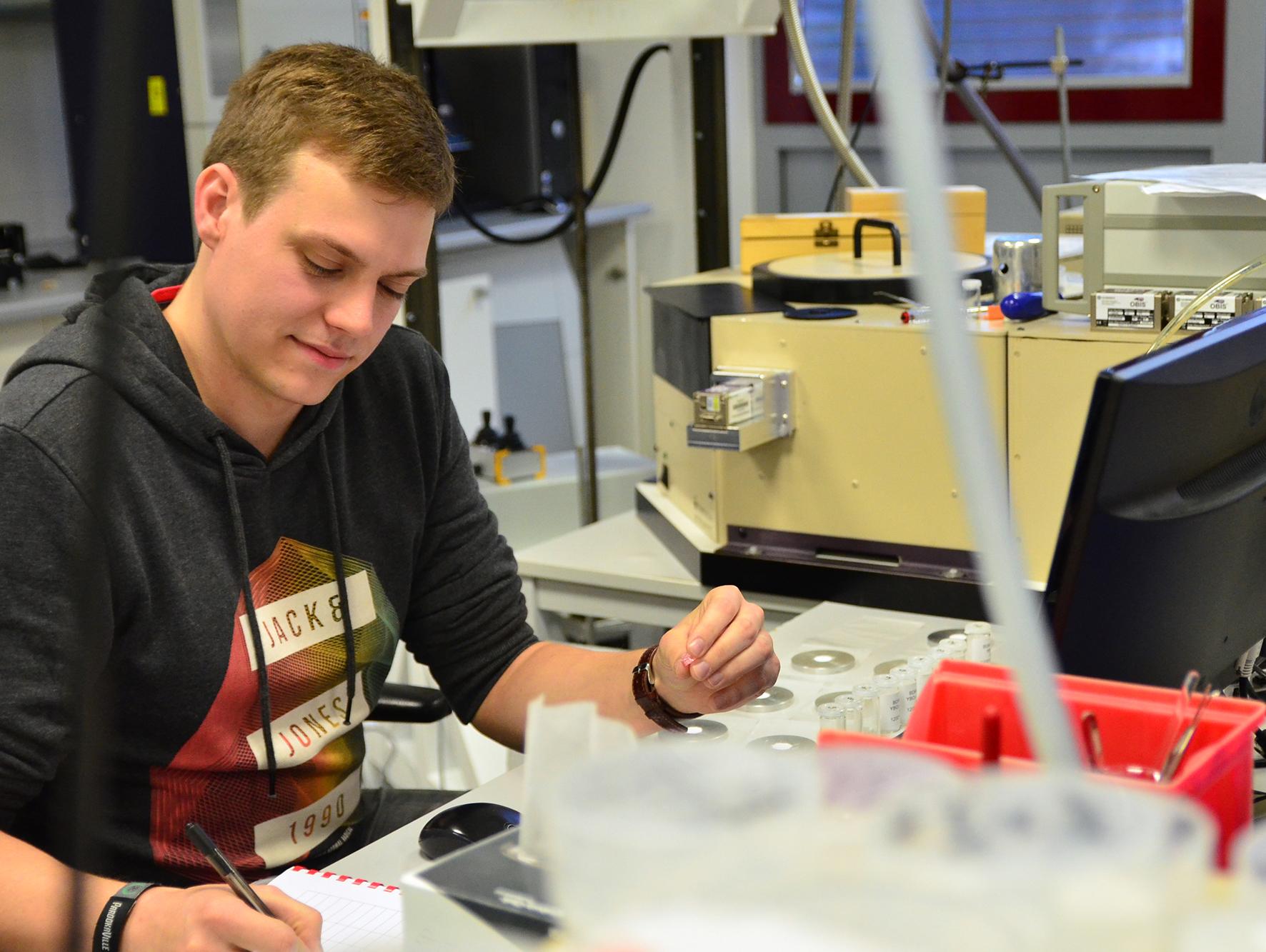 Patrick Pues sitzt schreibend im Labor vor dem Spektrometer und hält ein Kristall-Bruchstück in der linken Hand.
