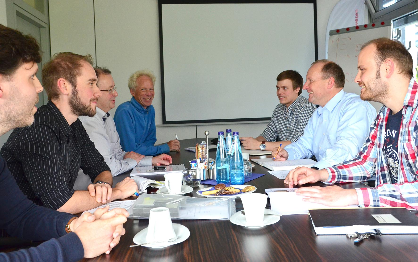 Gruppenfoto am Tisch in einer Konferenz