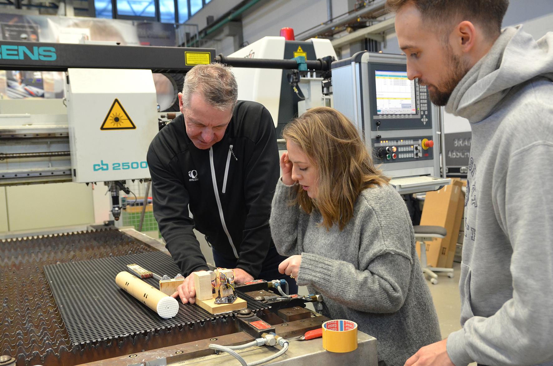 Jürgen Gröninger, Victoria Davalos und Frederik Kopatz platzieren den selbst gebauten Mikroprozessor an der Anlage für den Laser.