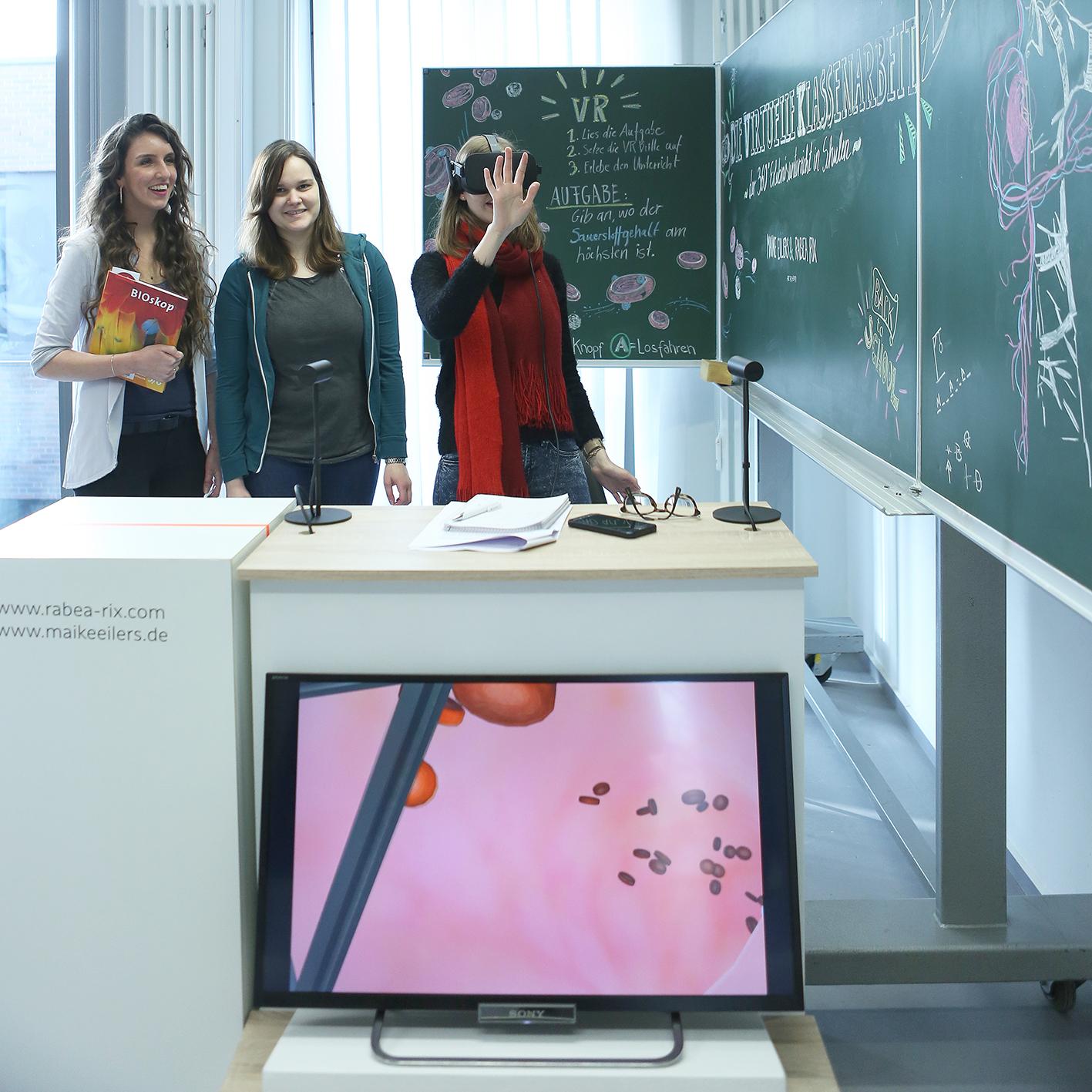 Rix, Eilers und Besucherin, die eine VR-Brille trägt. Auf einem Bildschirm darunter sieht man den roten Aderntunnel mit Blutkörperchen.