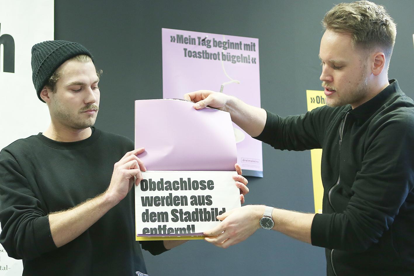 Kaiser und Reckel klappen eine Zeitungsseite aus ihrem Magazin aus.