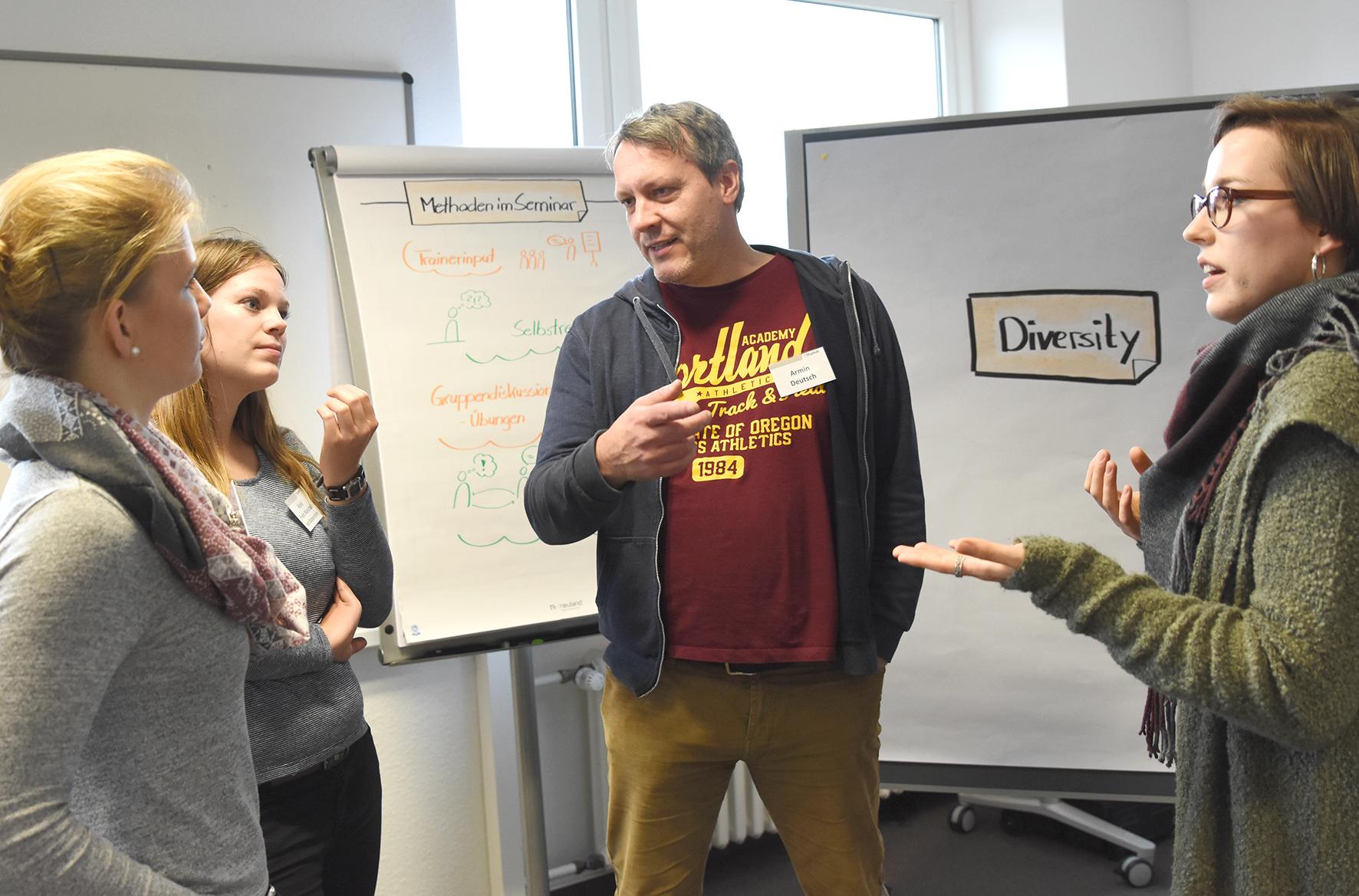 Eine Gruppe an Kursteilnehmern im intensiven Gespräch.