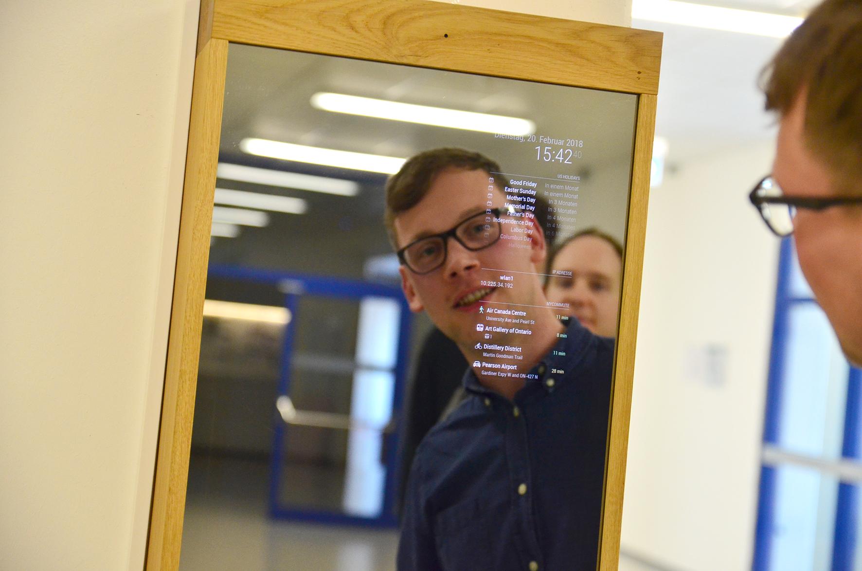 Student Robin Weiß vor dem Spiegel, auf der Spiegeloberfläche stehen digital Uhrzeit, Kalenderdaten und Feiertage