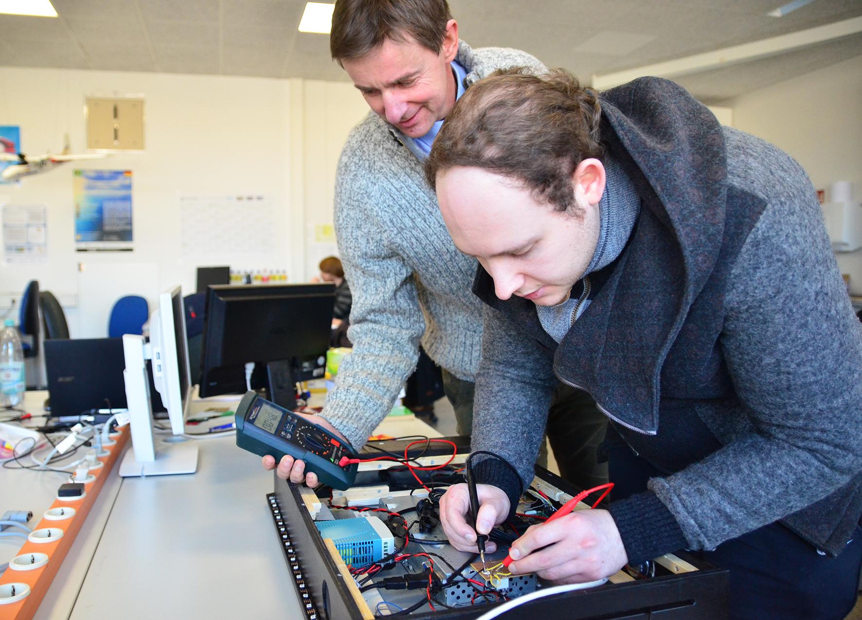 Student Lukas Scharlau lötet auf einer kleinen Platine der Elektrotechnik des Spiegels, Prof. Glösekötter überprüft die Versorgungsspannung