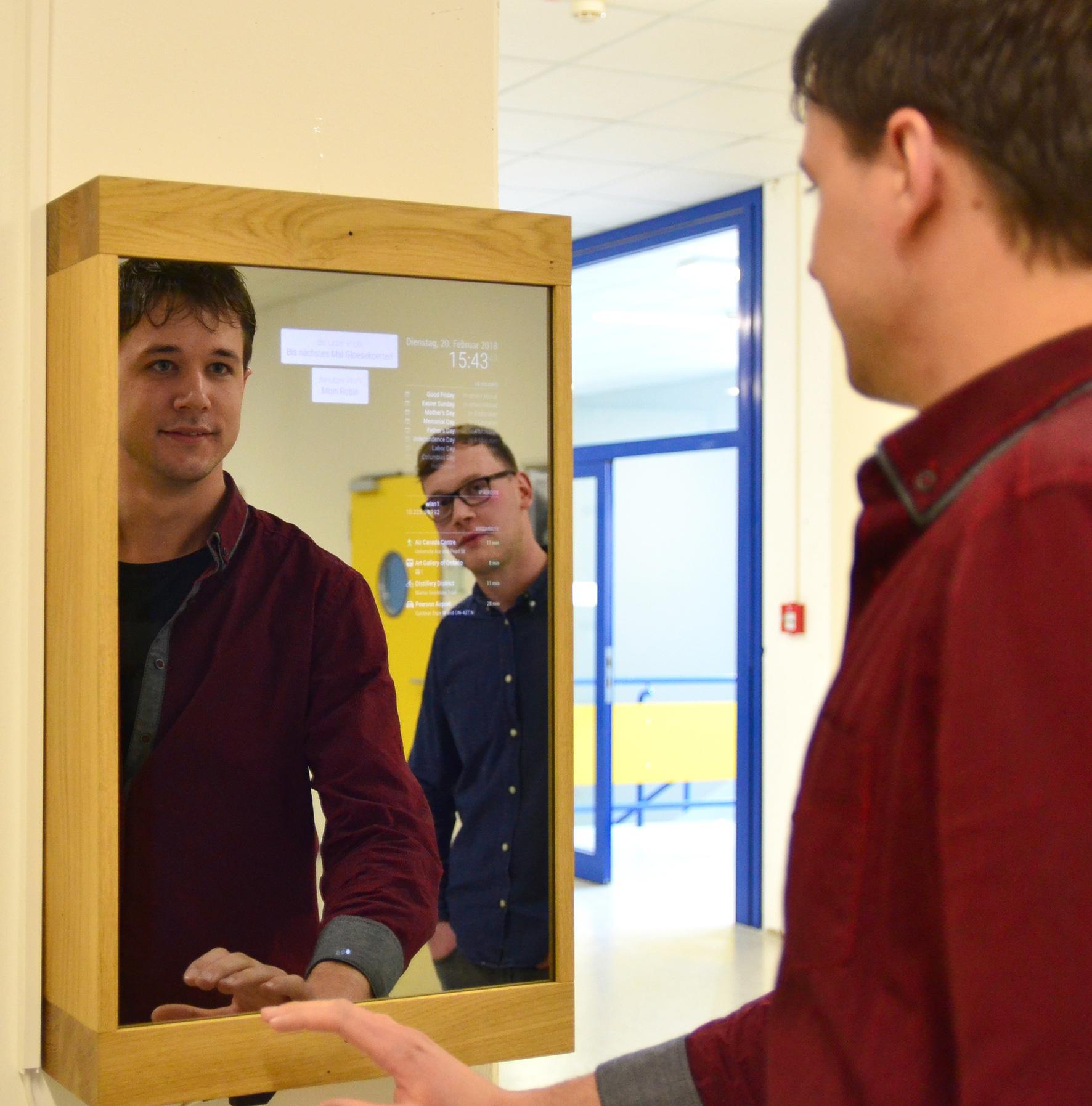 Student Kevin Ostenried macht vor dem Spiegel die Wischbewegung für eine andere Benutzeroberfläche