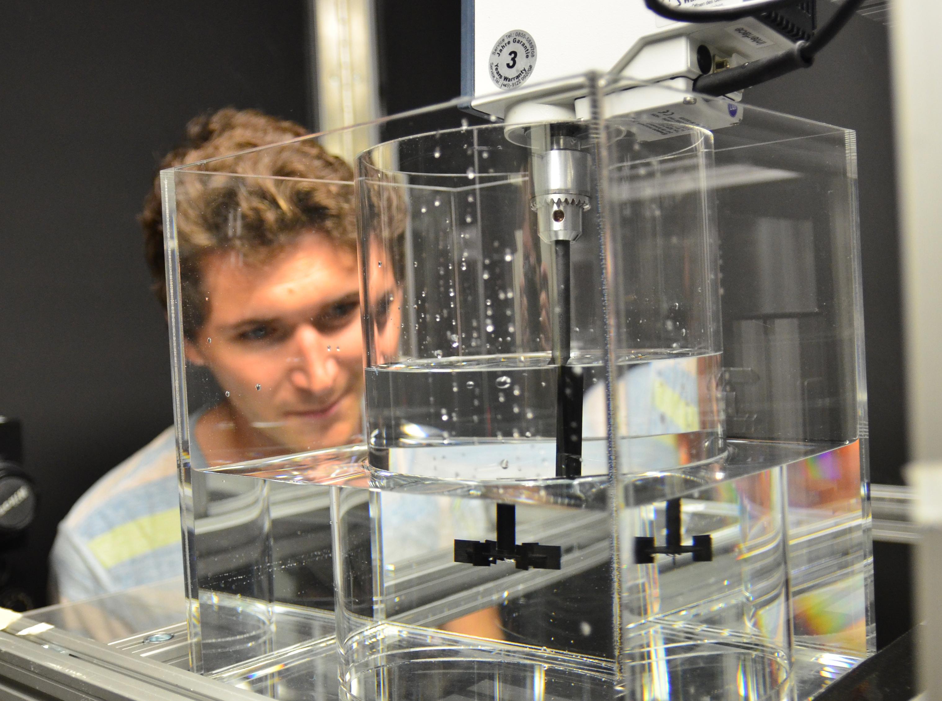 Sven Annas schaut in das Modell, das aus einem Standzylinder aus Plexiglas besteht.