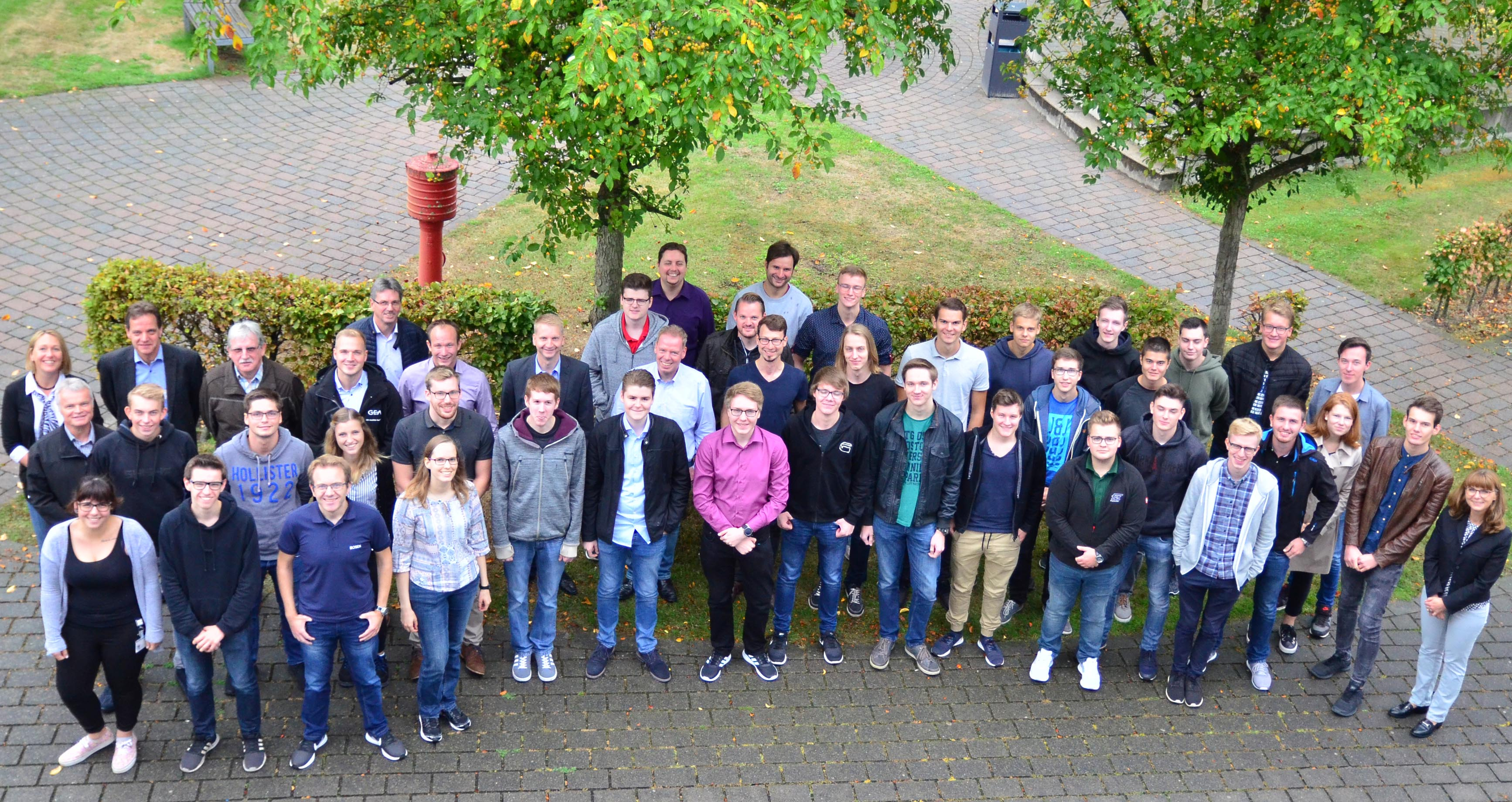 Gruppe Erstsemester mit Ausbildern auf Campusgelände