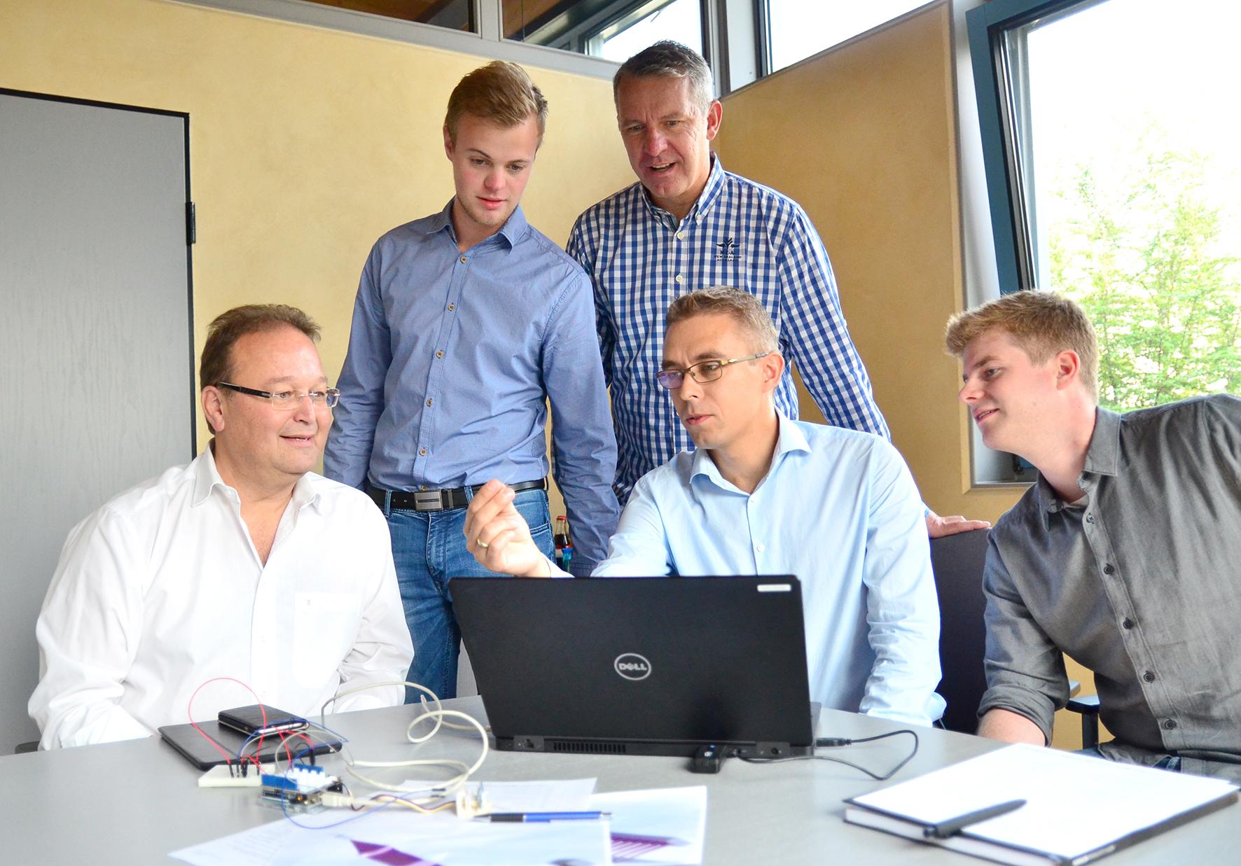 Helmut Teiting, Jan-Philipp Wessels, Jürgen Gröninger, Dennis Pollmann und Sascha Wagner diskutieren hinterm Laptop, Sascha Wagner hält ein Stück Folie in der Hand.