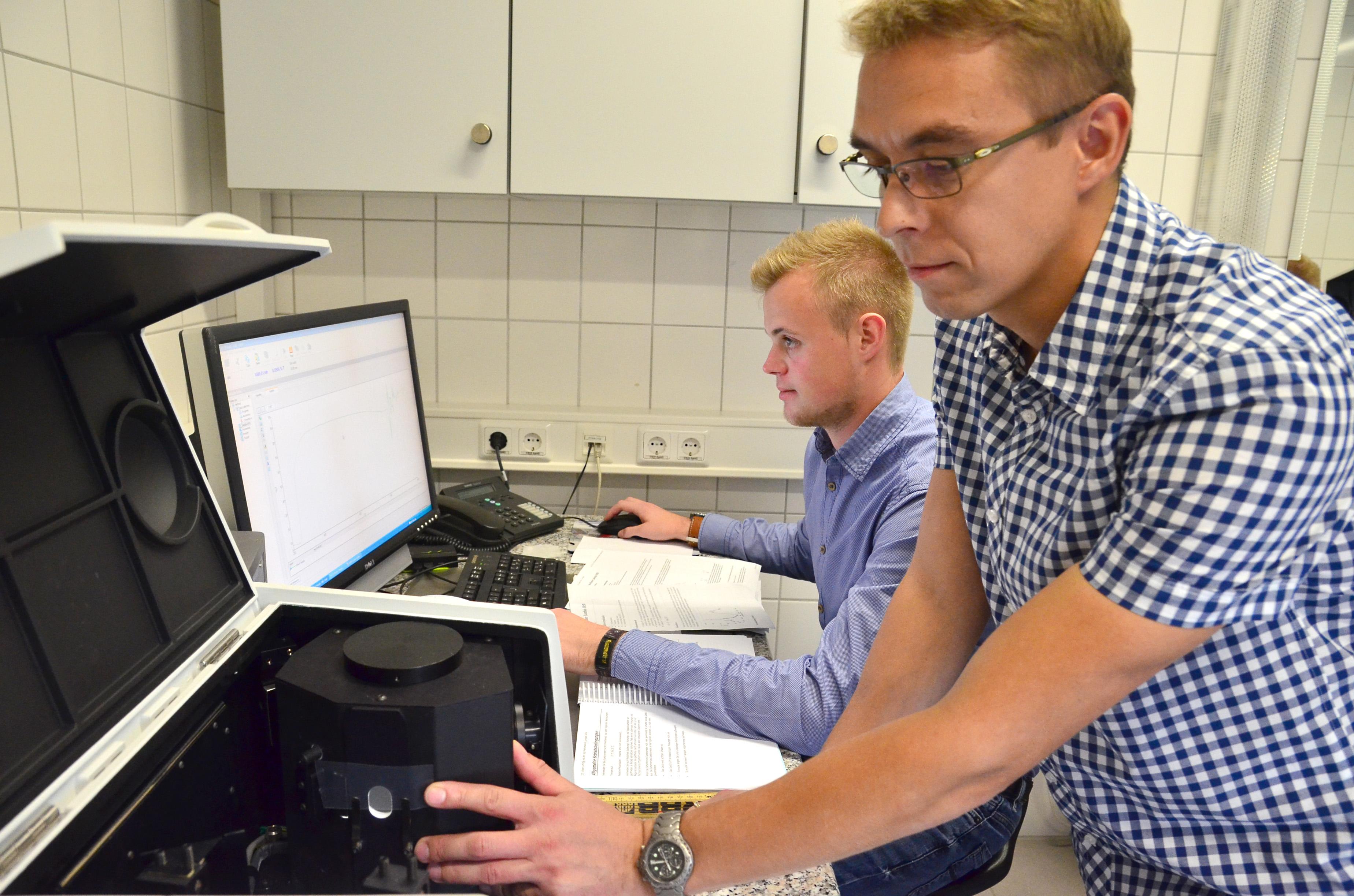 Sascha Wagner spannt Folie in ein Spektrometer ein, Jan-Philipp Wessels sitzt dahinter am PC und beobachtet den Bildschirm.