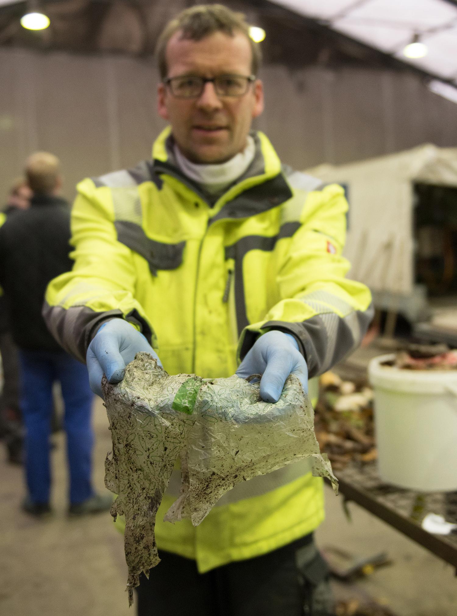 Thomas Bohmert hält Plastikreste in den Händen