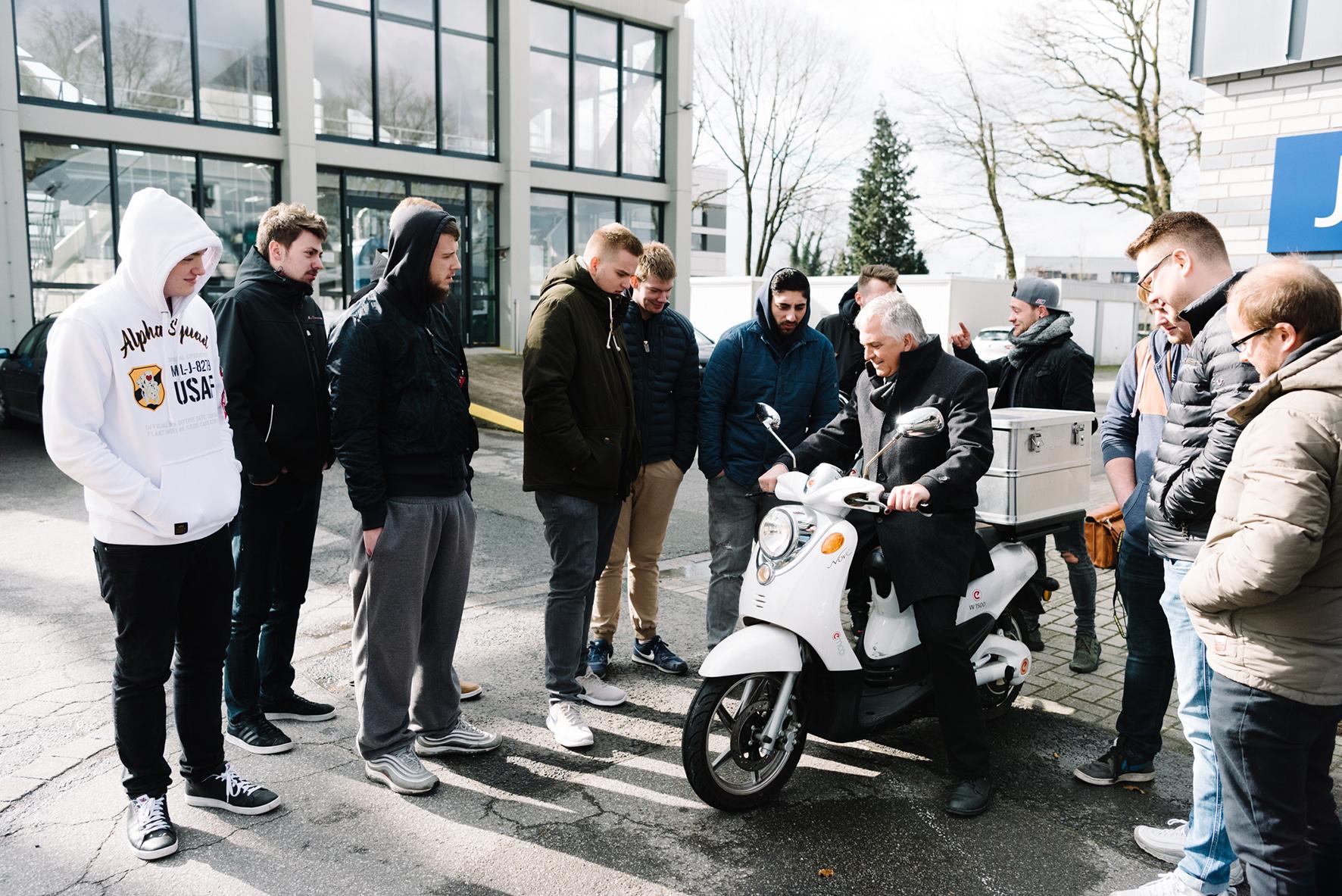 Prof. Wetter auf einem E-Roller, Schüler schauen und beobachten