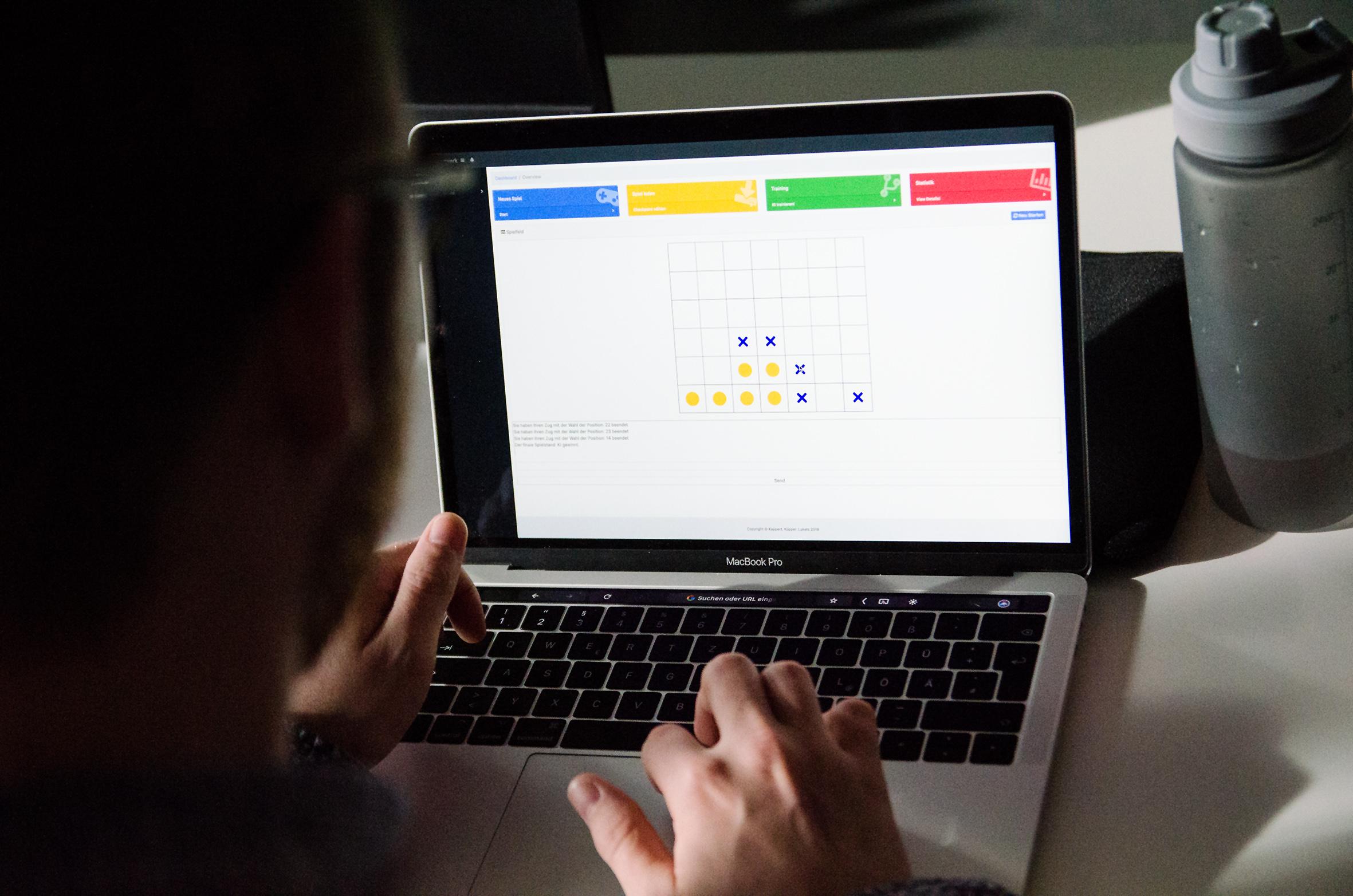 Student spielt Tic Tac Toe gehen eine KI auf seinem Laptop