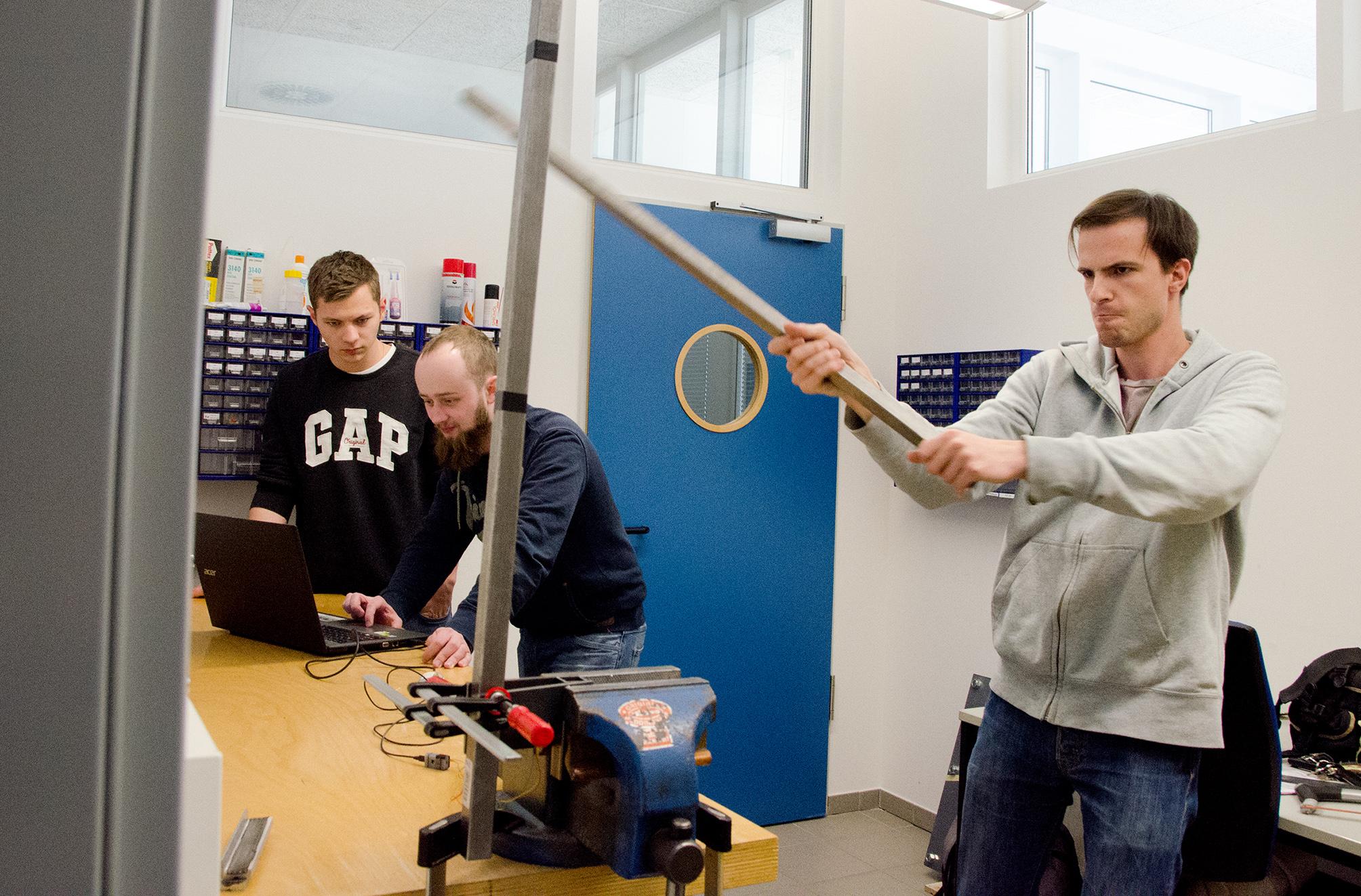 Lukas Fischer und Benjamin Roß messen die elektrische Spannung, die auf das Prothesen-Modell wirkt, Nils Knauseder imitiert mit einem Vierkantrohr Schwerthiebe.
