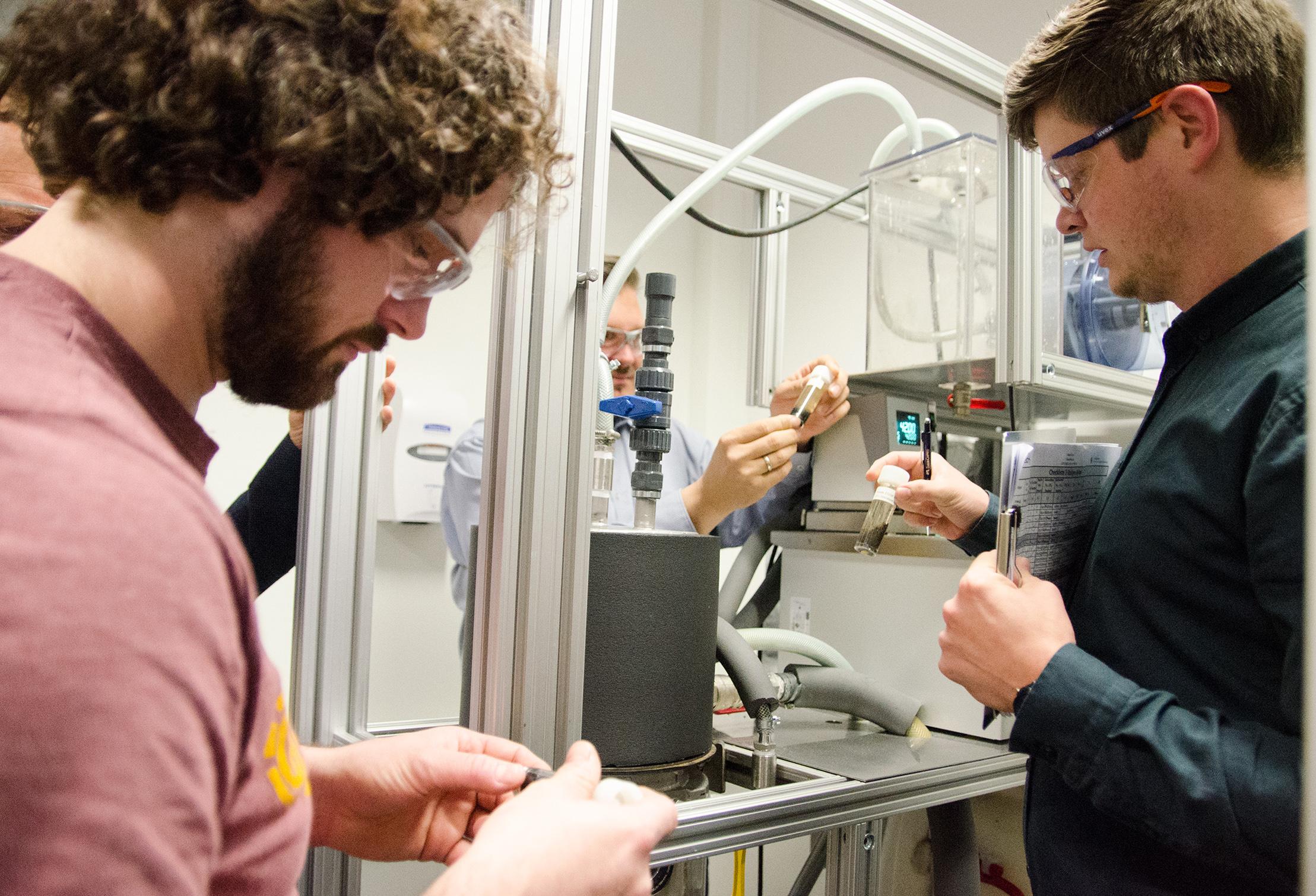 Drei Projektmitarbeiter am Reaktor