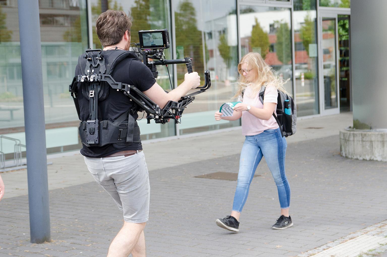 Protagonistin und Kameramann auf dem Campus beim Dreh