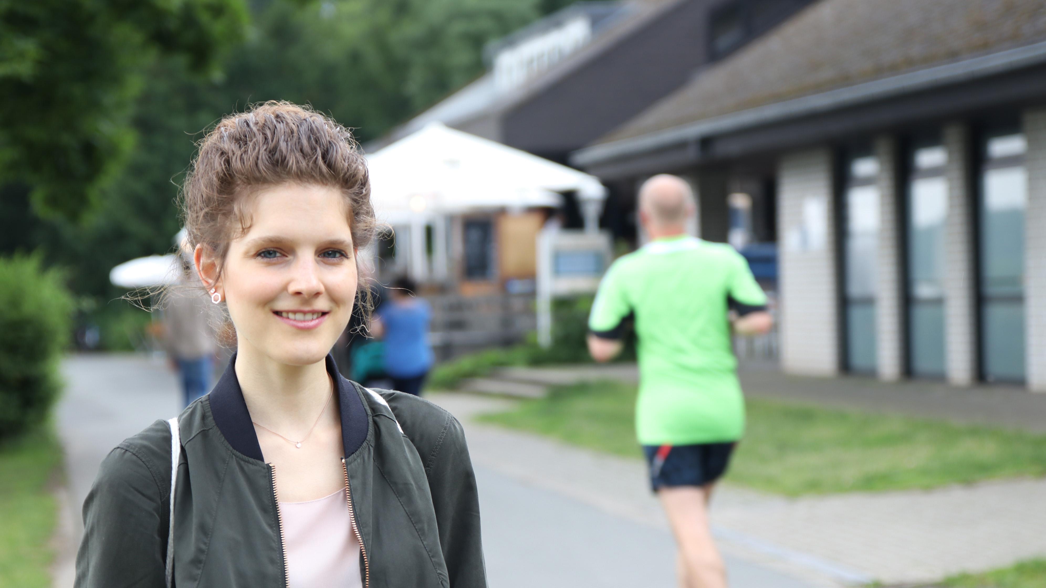 Christina Brachthäuser, Absolventin der FH Münster, steht am Aasee, rechts von ihr joggt ein Mann vorbei, hinter ihr ist eine Gaststätte.
