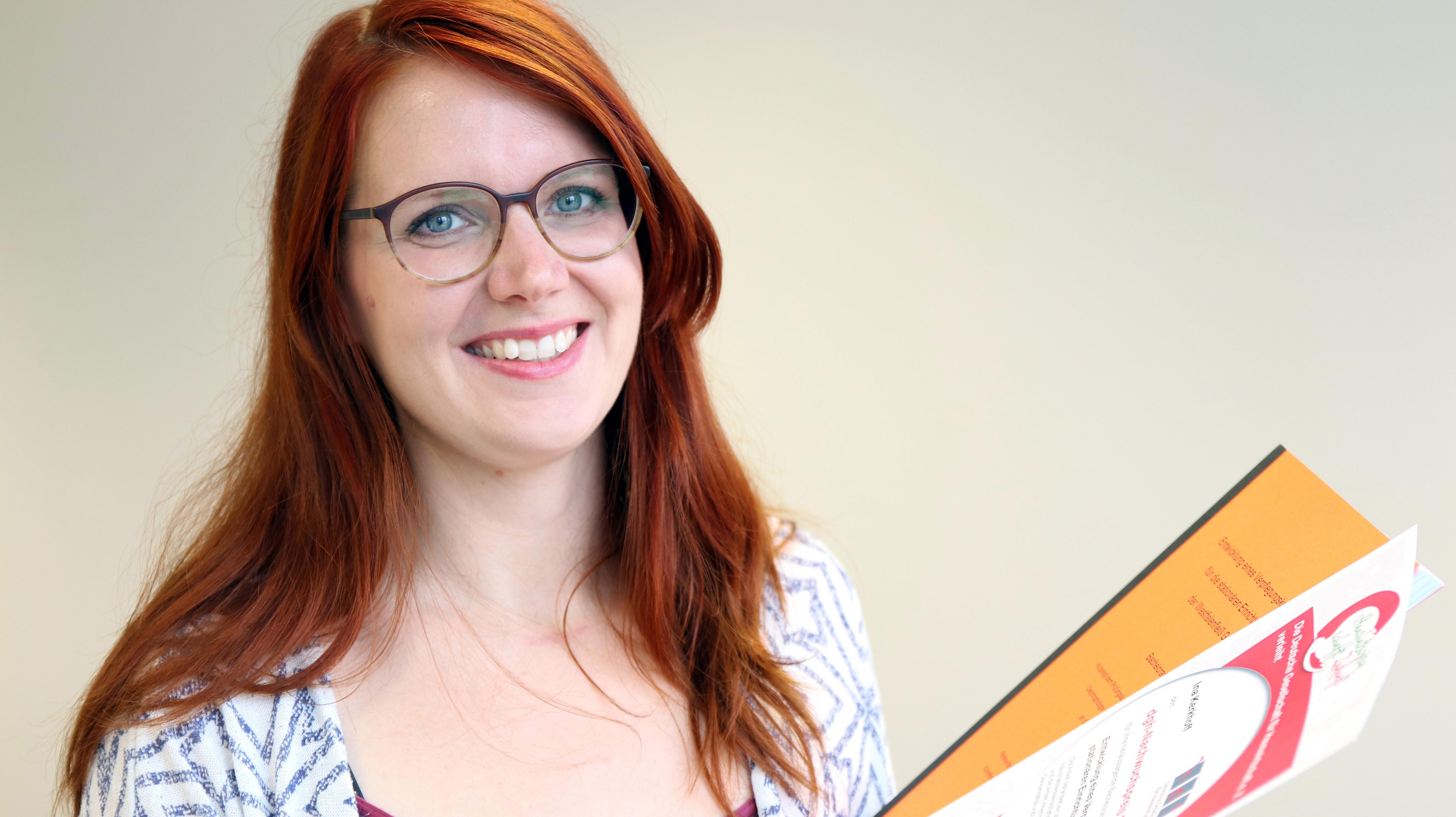 Die Studentin Ina Kerkhoff hält ihre Bachelorarbeit und eine Urkunde in der Hand.