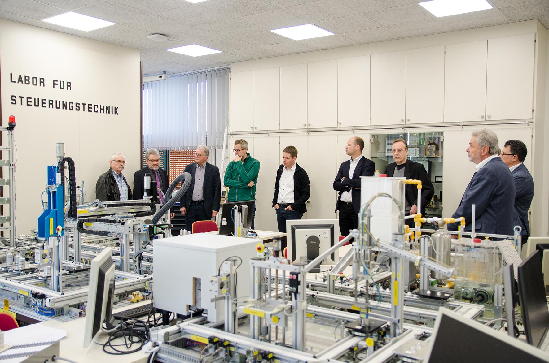 Professoren im Labor mit Modellfabrik