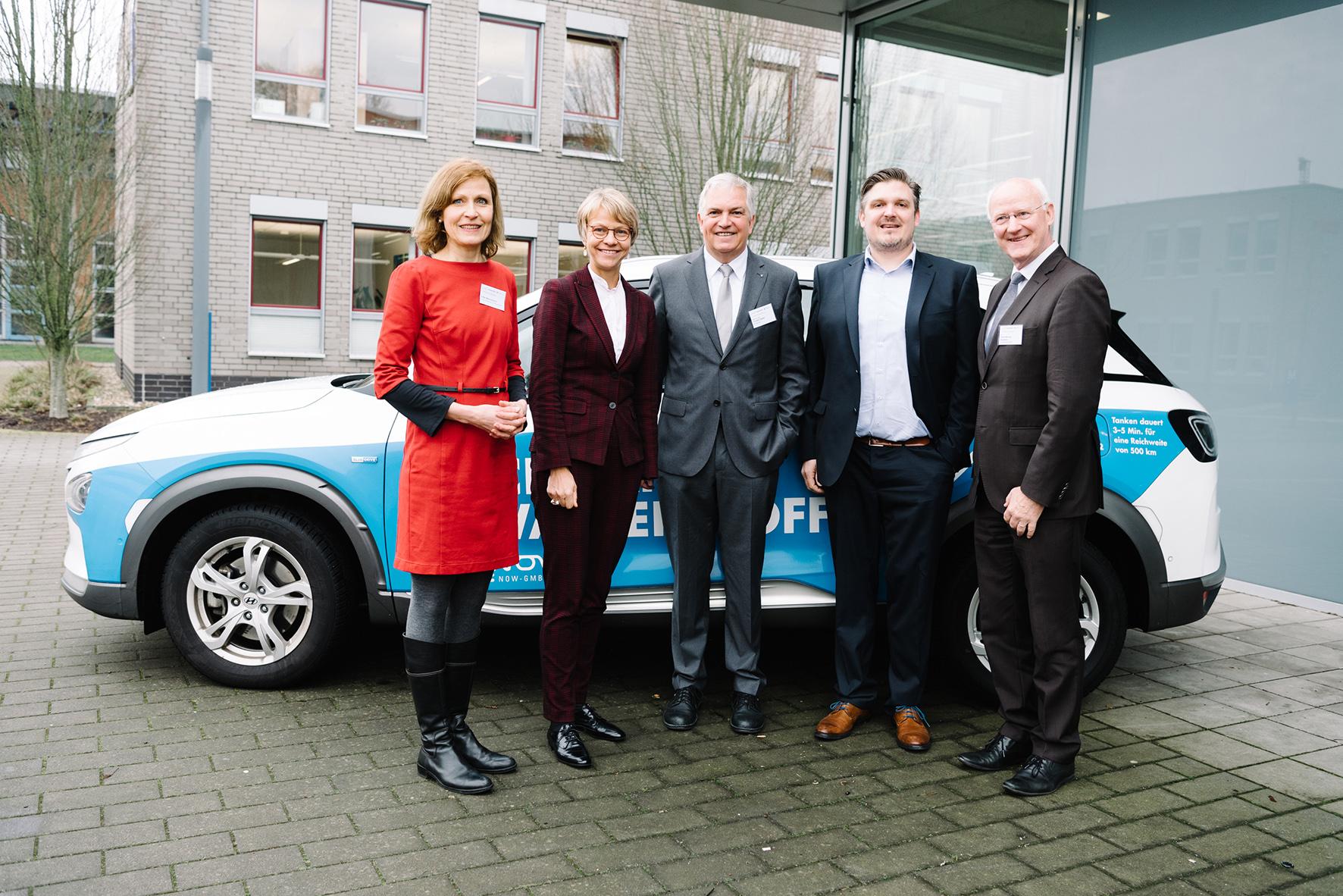 Gruppenbild vor Wasserstoff-Auto