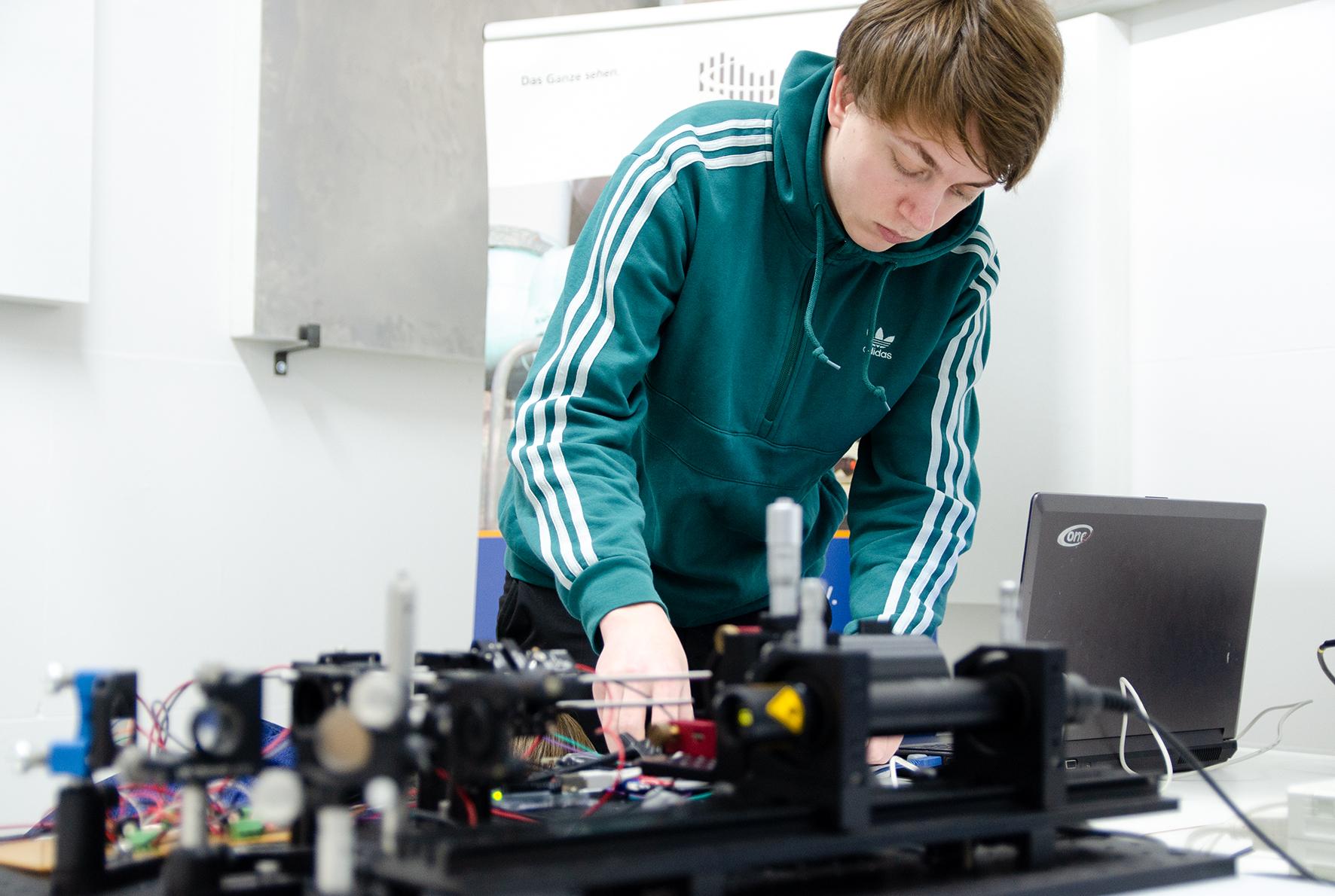 Student konzentriert sich und arbeitet am Laser-Vibrometer