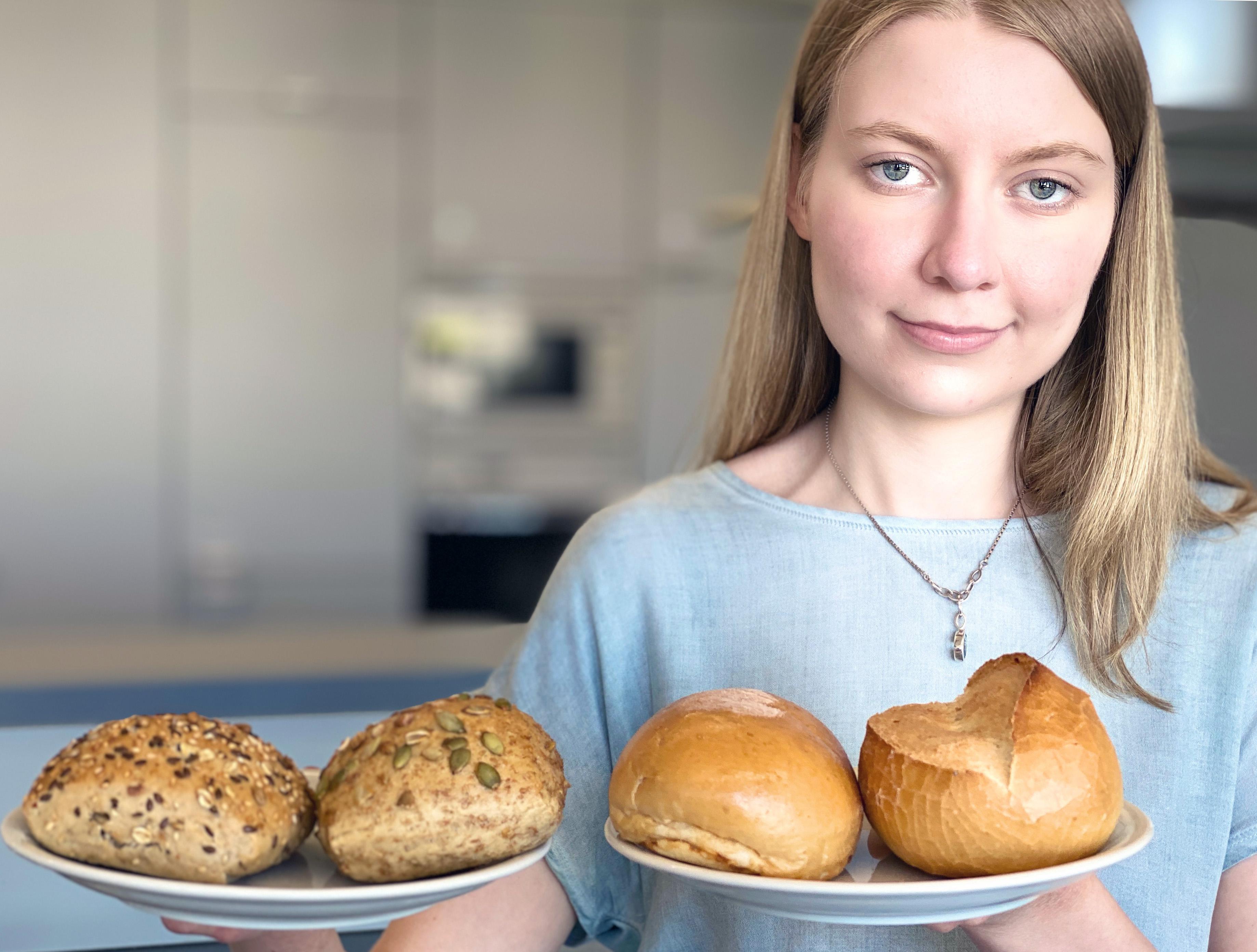 Fiona Abram steht mit Weizenbrötchen und Körnerbrötchen in einem Labor am Fachbereich Oecotrophologie – Facility Management.